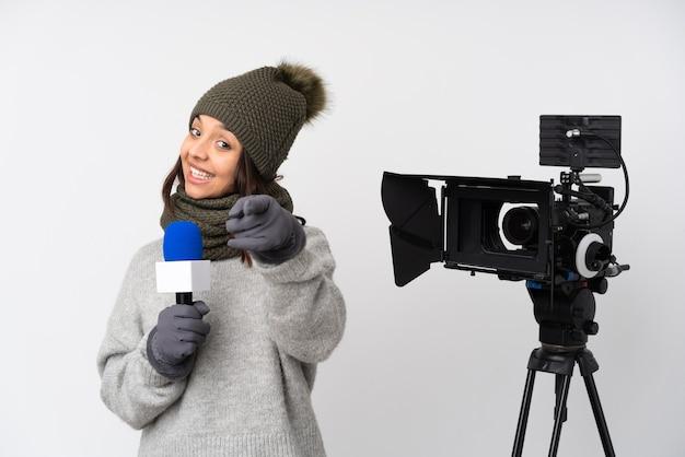 Reporterfrau, die ein mikrofon hält und nachrichten über isolierte weiße wand meldet, die telefongeste macht und nach vorne zeigt
