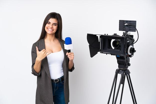 Reporterfrau, die ein mikrofon hält und nachrichten über isolierte weiße wand meldet, die telefongeste macht