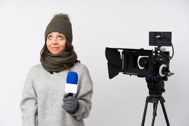 Reporterfrau, die ein mikrofon hält und nachrichten über isolierte weiße wand meldet und nach oben schaut