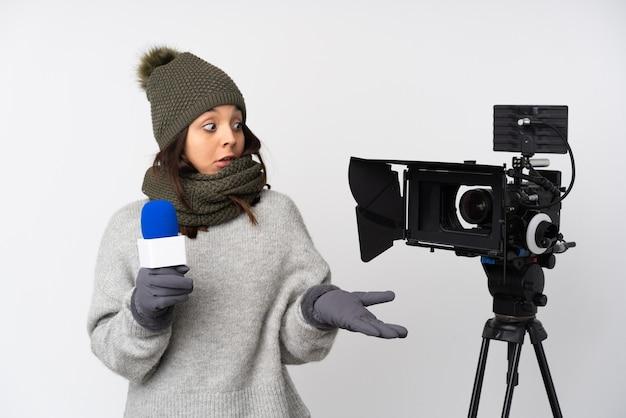 Reporterfrau, die ein mikrofon hält und nachrichten über isolierte weiße wand mit überraschendem gesichtsausdruck berichtet