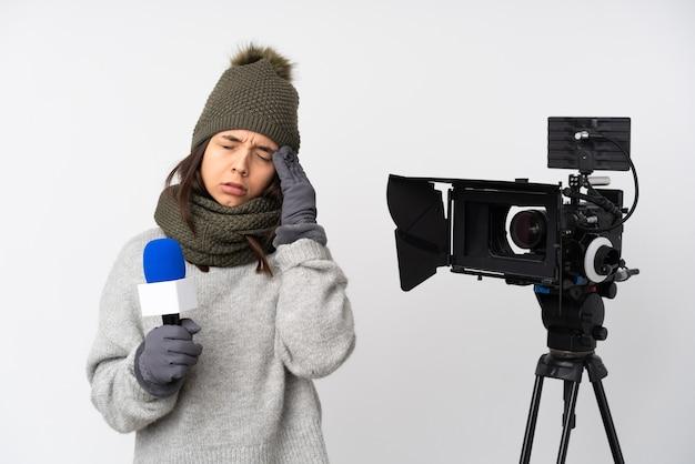 Reporterfrau, die ein mikrofon hält und nachrichten über isolierten weißen hintergrund mit kopfschmerzen berichtet