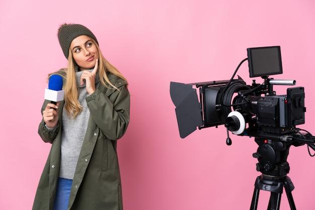 Reporterfrau, die ein mikrofon hält und nachrichten über isoliertes rosa berichtet, das zweifel beim aufblicken hat