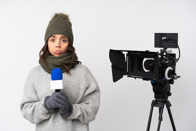 Reporterfrau, die ein mikrofon hält und nachrichten über isoliertes weiß berichtet, hält handfläche zusammen. person fragt nach etwas