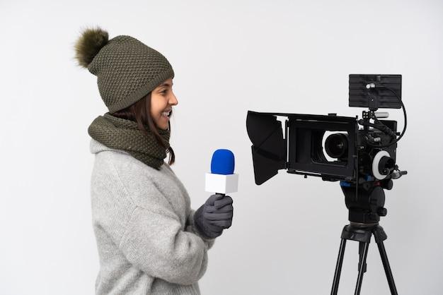 Reporterfrau, die ein mikrofon hält und nachrichten über isoliertes weiß in seitlicher position meldet