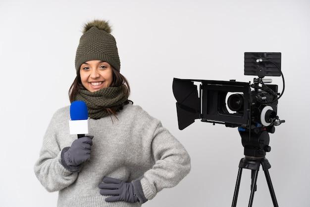 Reporterfrau, die ein mikrofon hält und nachrichten über isoliertes weißes aufstellen mit armen an der hüfte und lächeln berichtet