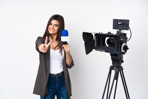 Reporterfrau, die ein mikrofon hält und nachrichten über isoliertes weißes lächeln berichtet und siegeszeichen zeigt