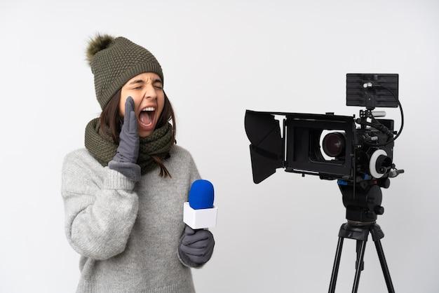 Reporterfrau, die ein mikrofon hält und nachrichten über isoliertes weißes schreien mit weit offenem mund zur seite berichtet