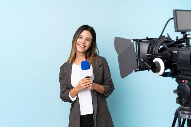 Reporterfrau, die ein mikrofon hält und nachrichten über lokalisiertem blauem wandapplaudieren berichtet