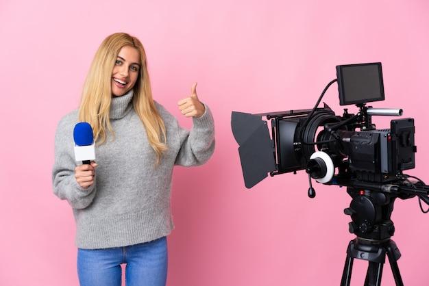 Reporterfrau, die ein mikrofon hält und nachrichten über rosa wand berichtet, die eine daumen hoch geste gibt