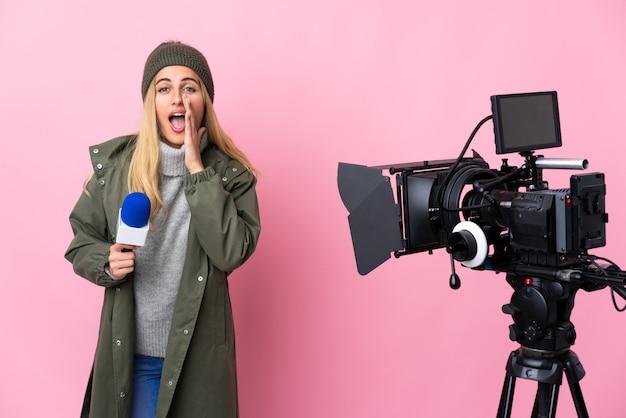 Reporterfrau, die ein mikrofon hält und nachrichten über rosa wand berichtet, die mit weit geöffnetem mund schreien