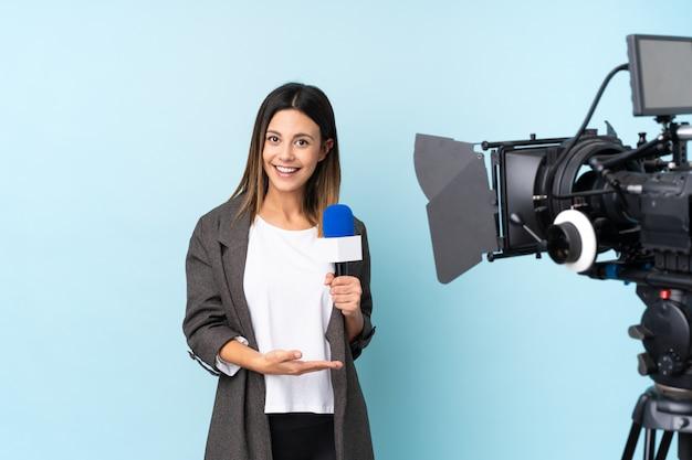 Reporterfrau, die ein mikrofon hält und über nachrichten berichtet, die hände zur seite für die einladung ausdehnen, um zu kommen