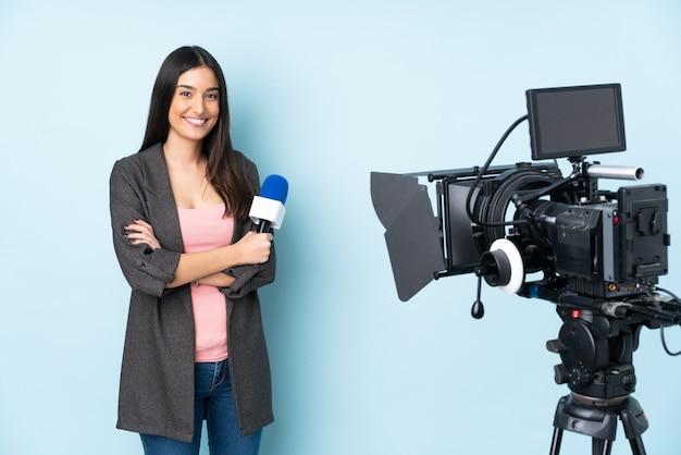 Reporterfrau hält ein mikrofon und berichtet nachrichten isoliert auf blauer wand, die arme in frontalposition verschränkt