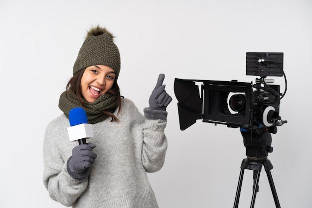 Reporterfrau hält ein mikrofon und berichtet nachrichten über isolierte weiße wand, die finger auf die seitenteile zeigt und glücklich ist