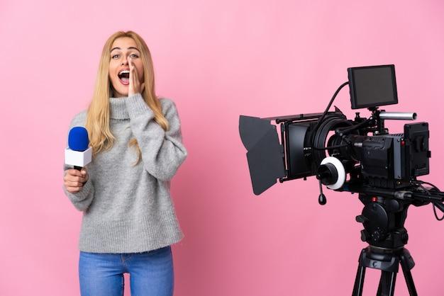 Reporterin, die ein mikrofon hält und nachrichten über isolierte rosa wand berichtet, die etwas schreit und ankündigt