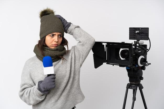 Reporterin, die ein mikrofon hält und nachrichten über isoliertes weiß berichtet, das zweifel hat, während sie kopf kratzen
