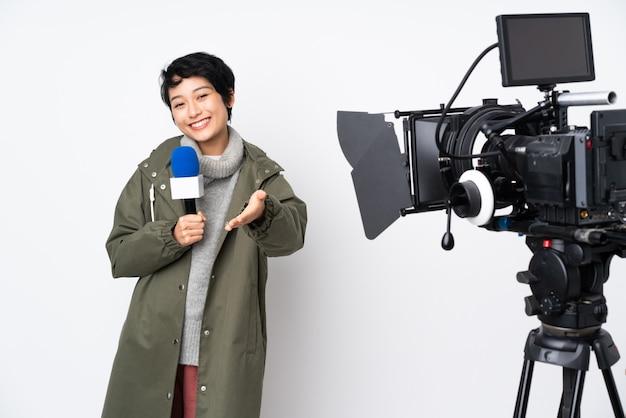 Reporterin, die ein mikrofon hält und über nachrichten berichtet, die sich die hände schütteln, um ein gutes geschäft abzuschließen