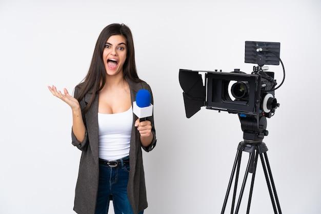 Reporterin hält ein mikrofon und berichtet nachrichten über weiße wand unglücklich und frustriert mit etwas