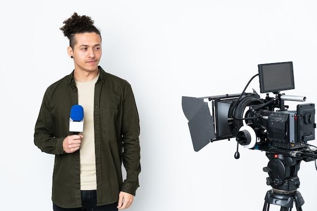 Reportermann, der ein mikrofon hält und nachrichten meldet, die stehen und zur seite schauen