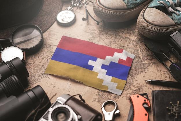 Republik-flagge nagornos karabach zwischen dem zubehör des reisenden auf alter weinlese-karte. touristisches bestimmungsort-konzept.
