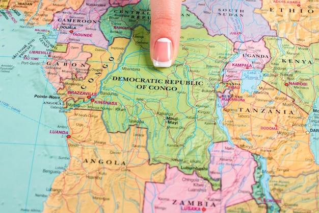 Republik kongo auf der karte. der finger einer frau, der auf den kongo zeigt. nation, die genug gelitten hat. gefährlicher ort zum leben.