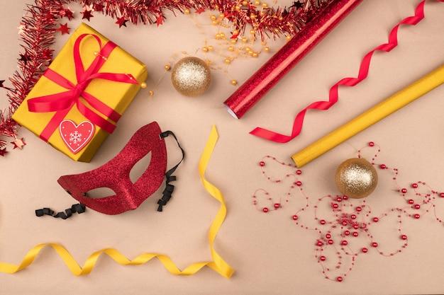 Requisiten für die. geschenke verpackt in einer gelben geschenkbox, eingewickelt in rotes band, geschenkverpackungsrollen, rote maskerademaske und weihnachtskugeln. neujahr. eine feier.