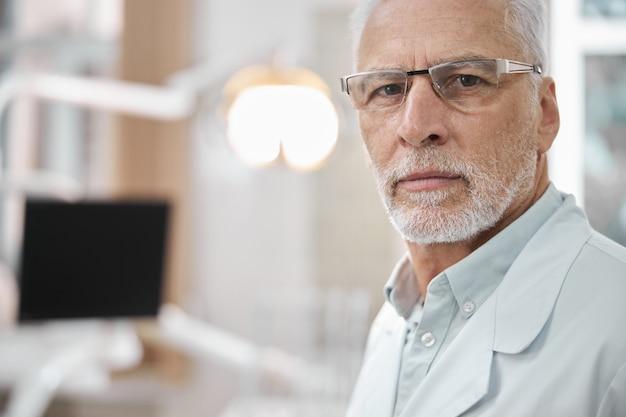Reservierter älterer mann mit brille und laborkittel, der in der zahnarztpraxis steht und in die kamera schaut