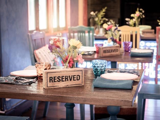 Reserviertes holzschild am esstisch im restaurant.