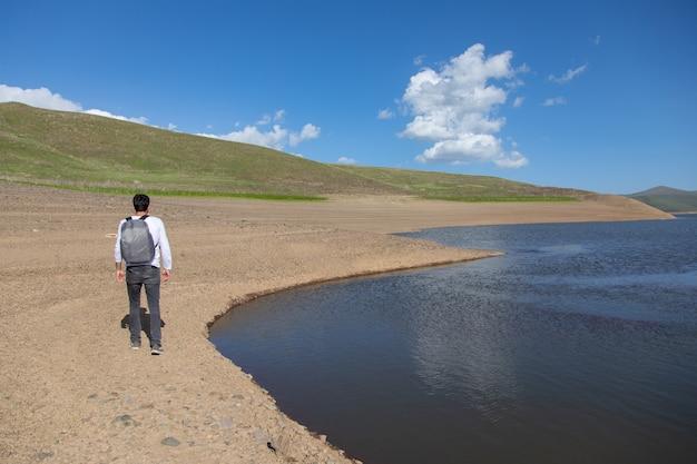 Reservoir mit reisemann unter abstraktem himmel