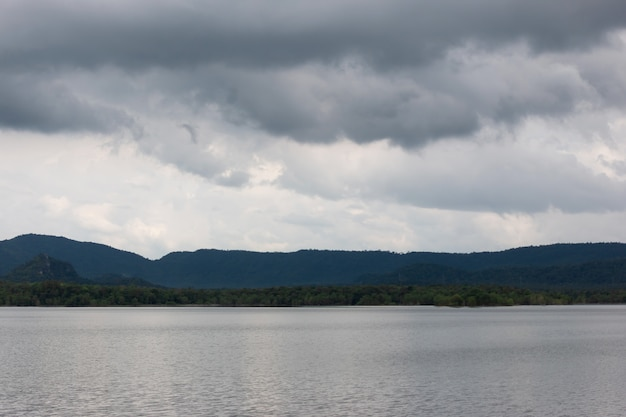 Reservoir umgeben von bergen und wolken vor dem regen