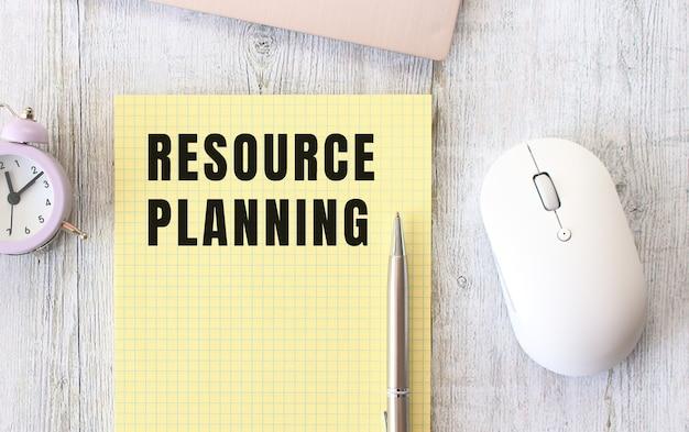 Ressourcenplanung text in einem notizbuch geschrieben, das auf einem hölzernen arbeitstisch neben einem laptop liegt. geschäftskonzept.