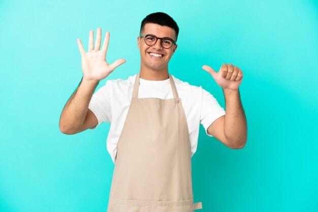 Restaurant-kellner-mann über isoliertem blauem hintergrund, der sechs mit den fingern zählt