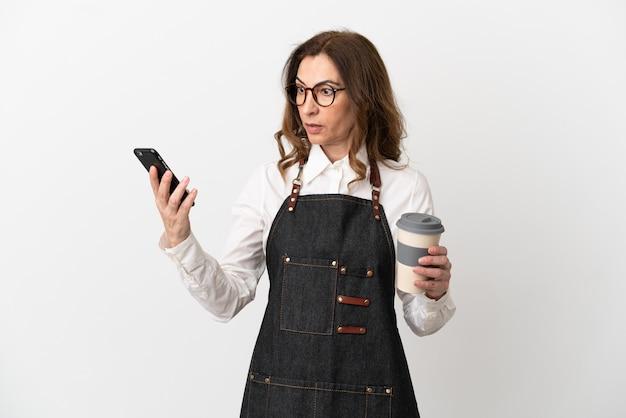 Restaurant kellnerin mittleren alters isoliert auf weißem hintergrund mit kaffee zum mitnehmen und einem handy