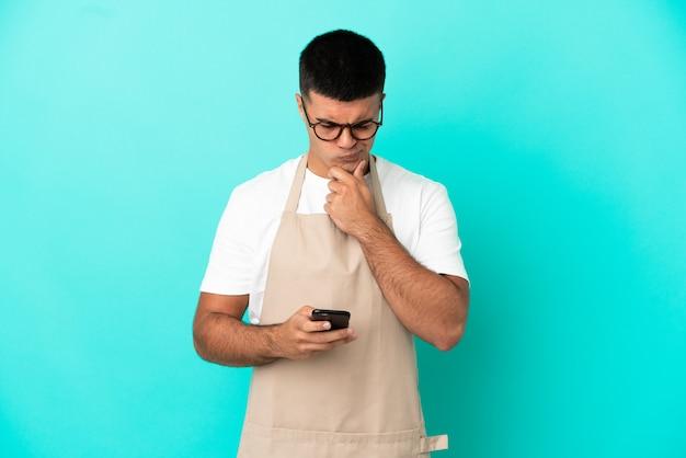 Restaurant-kellnermann über isoliertem blauem hintergrund, der eine nachricht denkt und sendet