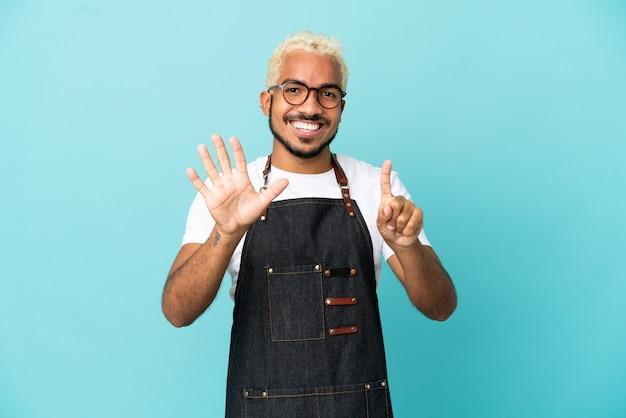 Restaurant kolumbianischer kellner mann auf blauem hintergrund isoliert, der sechs mit den fingern zählt