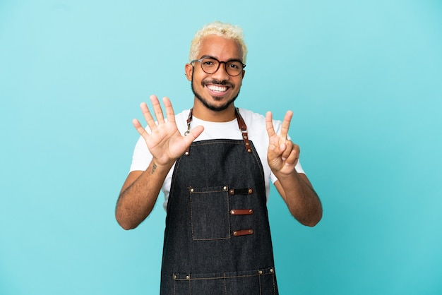 Restaurant kolumbianischer kellner mann auf blauem hintergrund isoliert, der sieben mit den fingern zählt