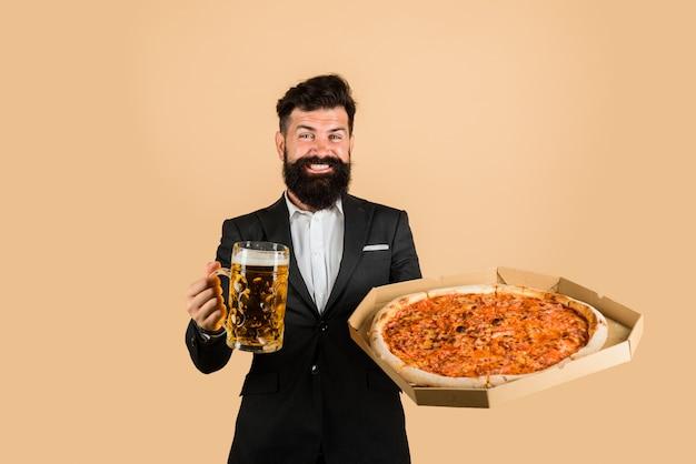 Restaurant oder pizzeria lächelnder mann mit bart hält köstliche pizza in schachtel und kaltes bier fast food