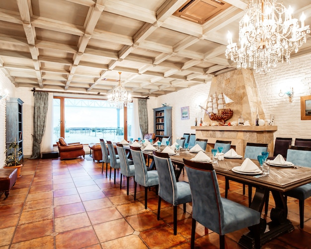 Restaurant privates zimmer mit blauen stühlen, weißen wänden, kamin und großem fenster