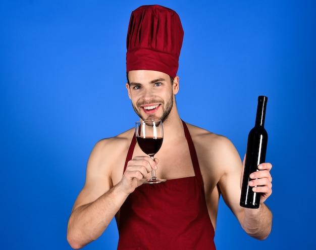 Restaurant. weinkeller. koch in schürze testet wein. bärtiger mann hält flaschenwein. männlicher sommelier, der rotwein verkostet. wein machen. restaurantkonzept. auf blauem hintergrund isoliert. platz kopieren.