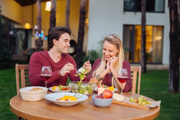 Restaurantessen. freudiges glückliches paar, das zusammen sitzt, während ein köstliches abendessen im restaurant hat