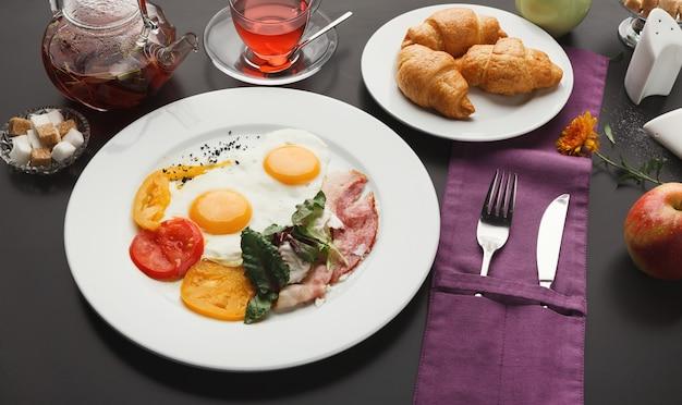 Restaurantfrühstück mit speck und spiegeleiern