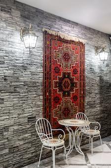 Restauranthalle mit grauer steinmauer, verziert mit aserbaidschanischem teppich