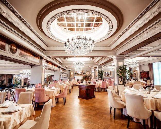 Restauranthalle mit runden und quadratischen tischen, einigen stühlen und pflanzen
