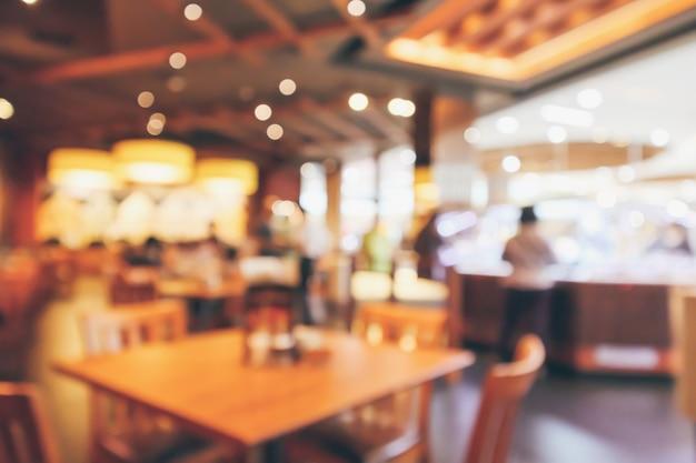 Restaurantinterieur mit kunden- und holztisch verwischen abstrakten hintergrund mit bokeh-licht