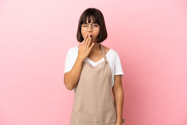 Restaurantkellner über isoliertem rosa hintergrund gähnend und mit weit geöffnetem mund mit der hand bedeckt