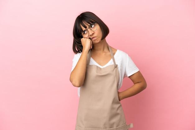 Restaurantkellner über isoliertem rosa hintergrund mit müdem und gelangweiltem ausdruck?