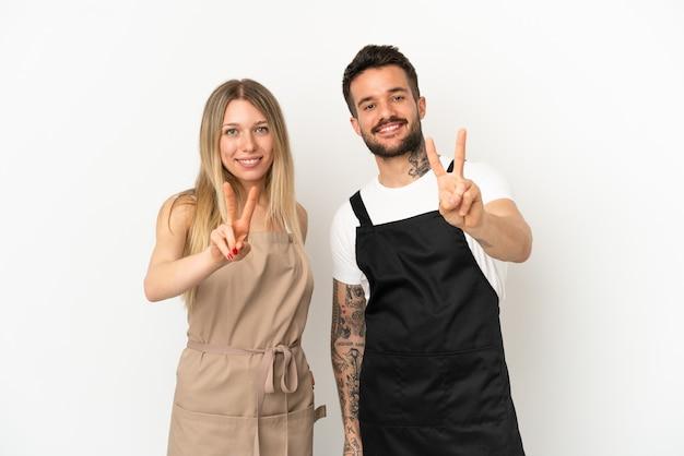 Restaurantkellner über isoliertem weißem hintergrund lächelt und zeigt victory-zeichen