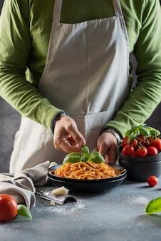 Restaurantkonzept. mann, der italienische spaghetti mit tomate und basilikum, selektives fokusbild kocht