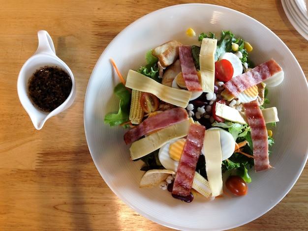 Restaurantlebensmittel, caesar-salat, lokalisiert am holztisch, draufsicht