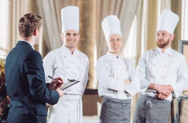 Restaurantleiter und sein personal in der küche. interaktion mit dem küchenchef in der gewerblichen küche.