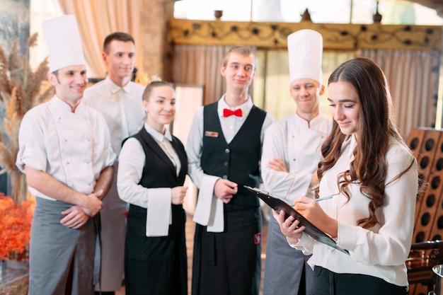 Restaurantleiter und seine mitarbeiter in der küche. interaktion mit dem küchenchef in der gewerblichen küche.